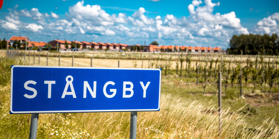 Nybyggda hus på rad i bakgrunden, i förgrunden en blå trafikskylt som det står Stångby på.