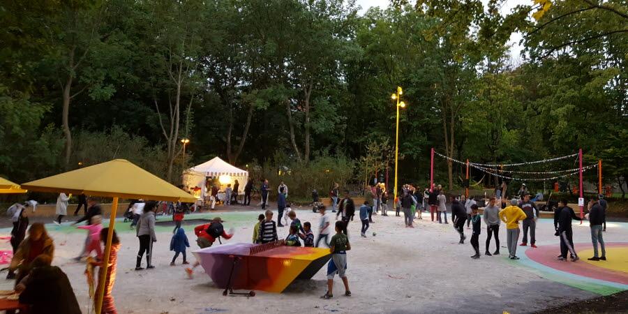 Utomhuspark med parasoll, pingisbord, beachplaner och ett tält, där flera människor umgås i kvällsljus.