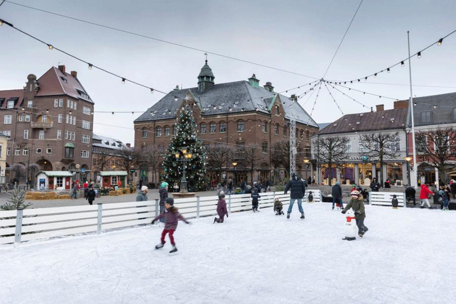 Barn som åker på en isbana, julgran i bakgrunden.