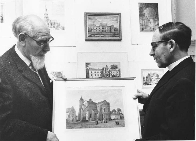 två män med glasögon och kostym håller en tavla med ett gammalt hus mellan sig.