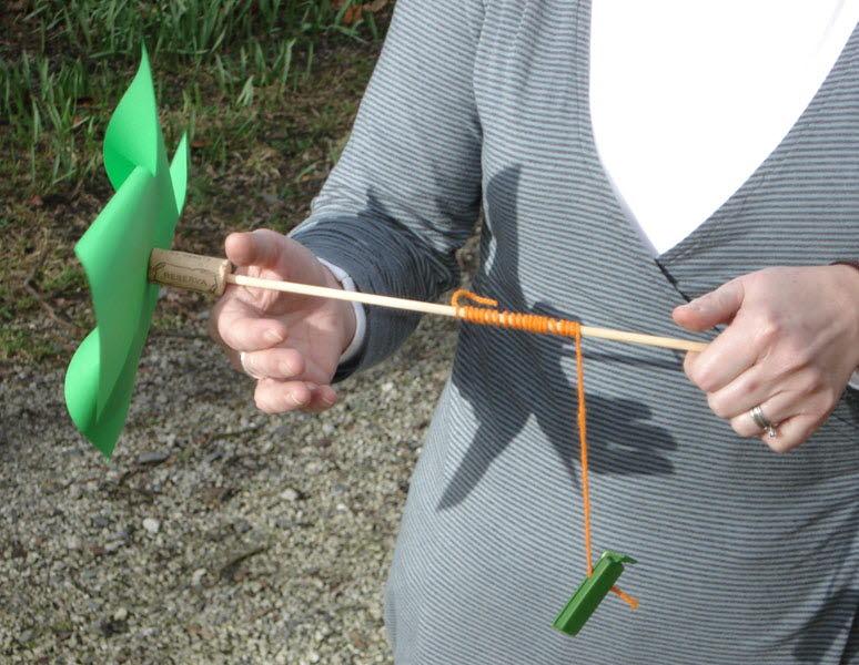Två händer håller en vindsnurra gjord av papper, kork och garn