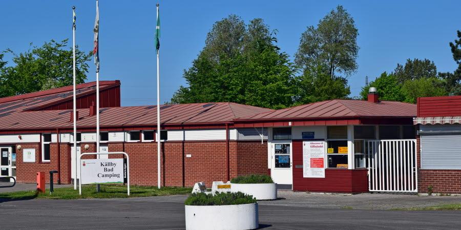 Entrén till Källby camping och friluftsbad, en röd tegelfärgad byggnad med flaggstänger framför och stora krukor med växter.