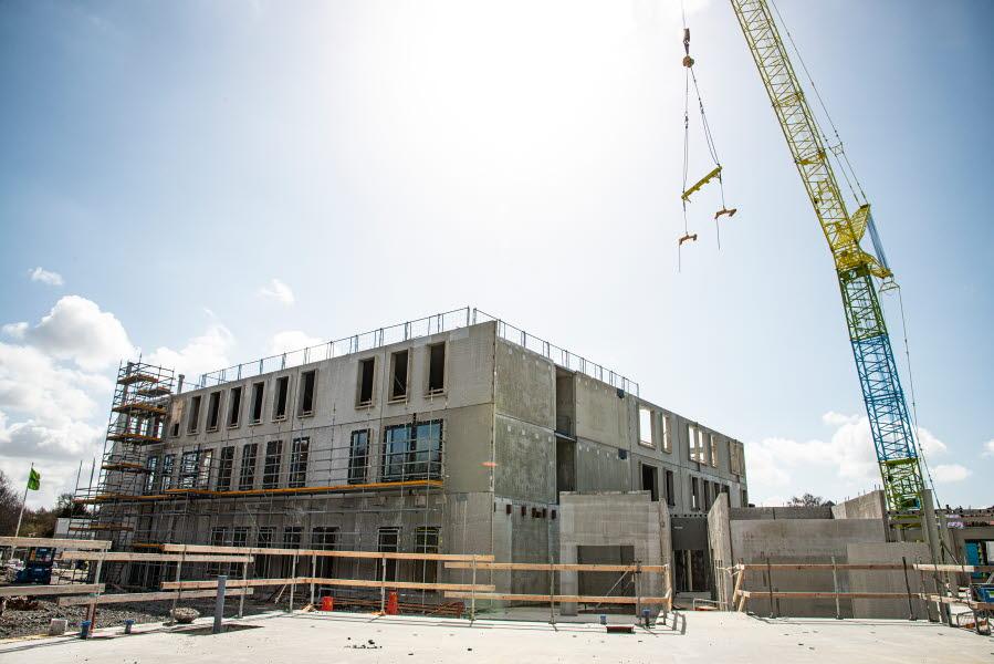 Bygge av en ny skola i tre våningar med hjälp av stor byggkran.
