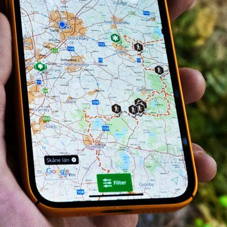 En smartphone med en karta som visar naturområden. Personen som håller i telefonen är i skogen.