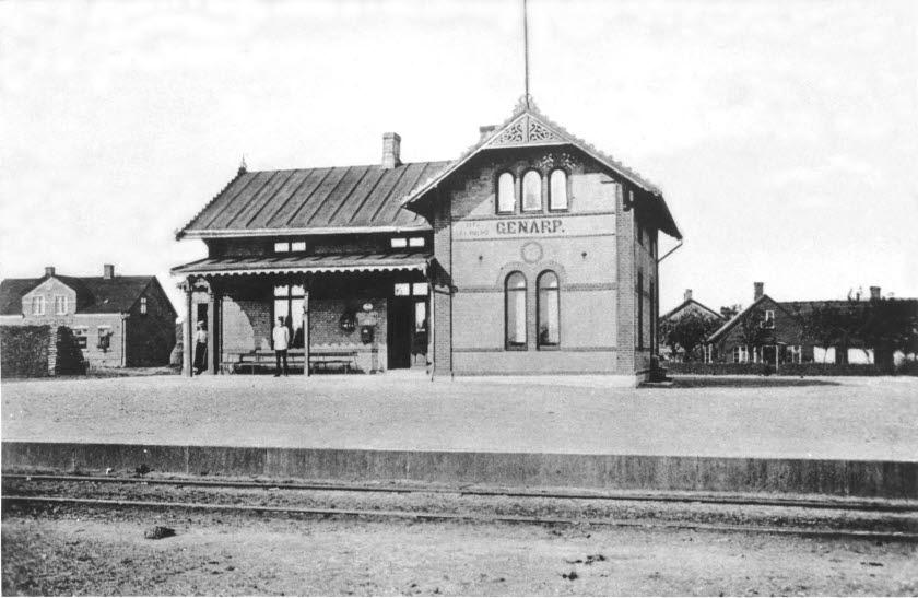 Stationshus i sten. Svartvit bild där det står Genarp på byggnadens fasad.