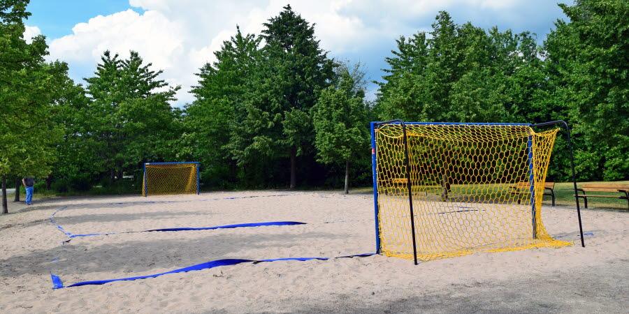 Beachplan med gulblåa mål för fotboll i ljus finkornig sand.