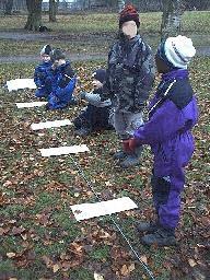 Fyra barn har placerat ut planeternas läge längs ett snöre på marken.