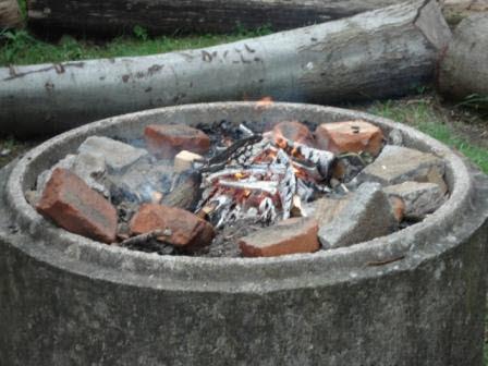 En eld i en eldstad av cementrör med tegelstenar runt