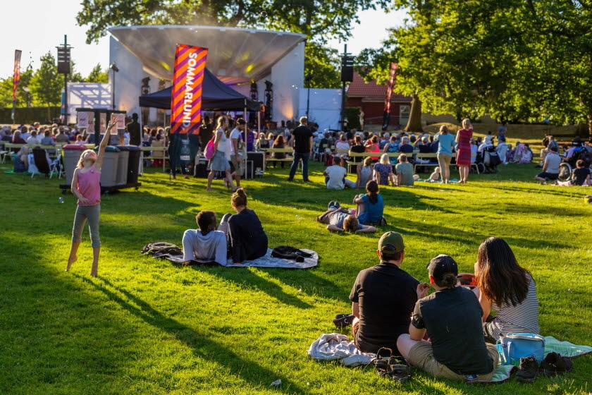 Personer på picknickfiltar och stolar på en gräsmatta framför en vit scen i en park.