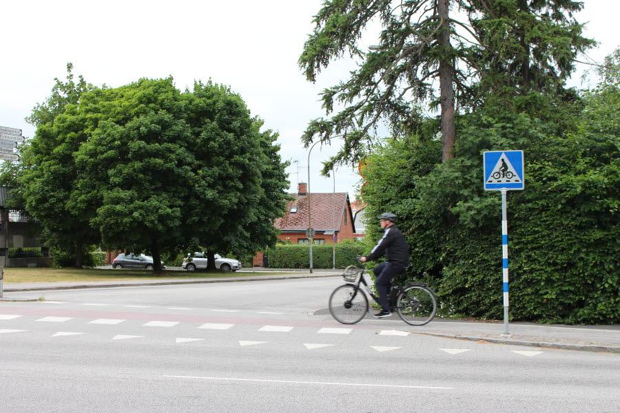 Man på cykel ska precis korsa en cykelöverfart.